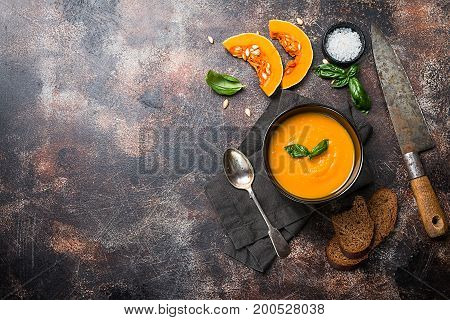 Pumpkin and carrot soup with cream and basil in black plate over dark background Top view Copy space
