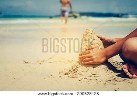 The child is sitting in the sand beside the sea.