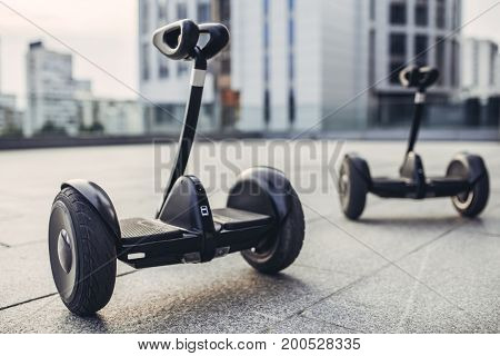 Two gyro scooters are standing on the street. Couple of gyro scooters in the background of city.