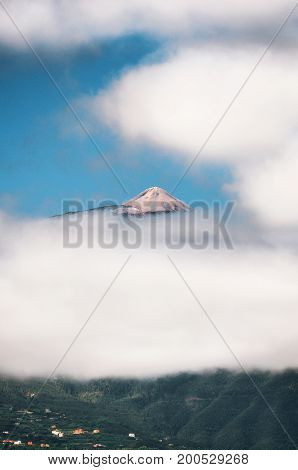 Peak of Teide Top of Teide in clouds with the village and greenery hills in bottom. View from Puerto de la Cruz Tenerife Canary islands Spain