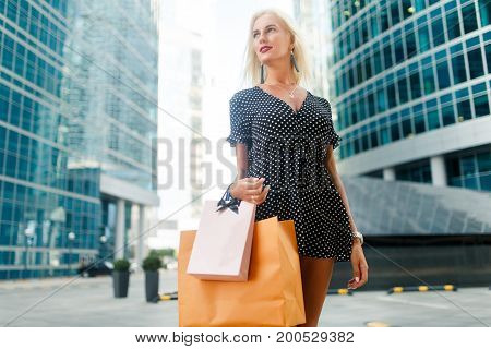 Photo of girl on shopping with purchases on street near buildings during day