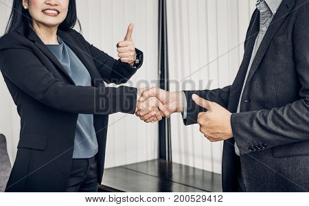 Smile Business woman and business man shaking hand and thumb up in office Partnership agreement concept Good solutions.