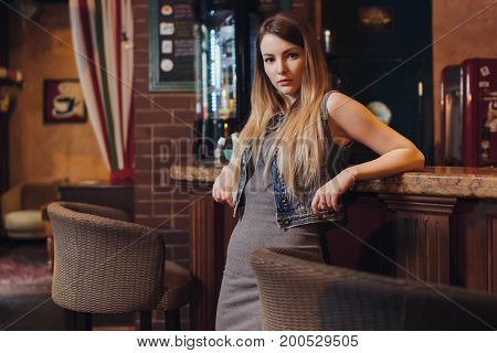 Portrait of young female model with fair hair leaning her elbows on bar counter looking at camera in vintage restaurant.