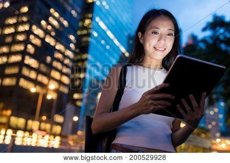 Business woman using tablet computer at night