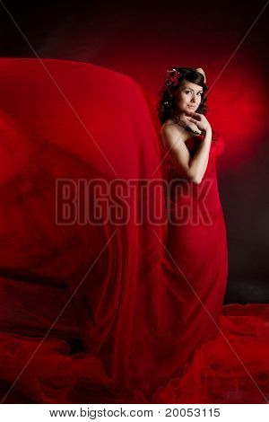 Beautiful Woman In Red Waving Flying Dress. Looking At Camera.