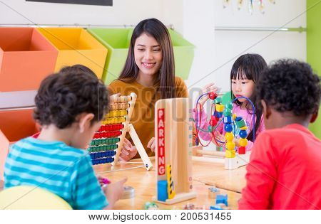 Asian female teacher teaching mixed race kids play toy in classroom. Kindergarten pre school concept.