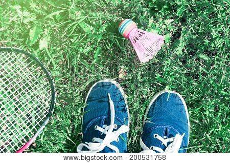 A pink shuttlecock and a badminton racket lie on the green lawn grass at the player's feet in blue sports shoes.