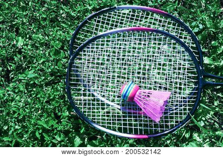 A pink shuttlecock and a badminton racket lie on the green lawn grass.