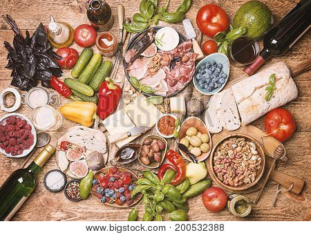 Top view table full of food. Italian antipasti wine snacks set. Cheese variety, nuts, Mediterranean olives, sauces, Prosciutto di Parma or jamon, tomatoes, vegatables and berries and wine over wooden background