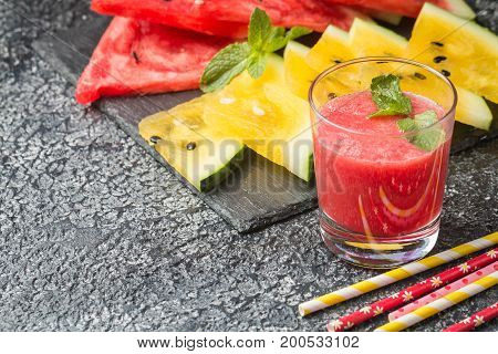Glass of fresh red watermelon juice with slices of red and yellow watermelon. Healthy eco sweet food rich in vitamins.