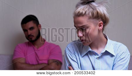 Young couple having relationship problems. Man and woman sitting separately in their living room. Focus on female