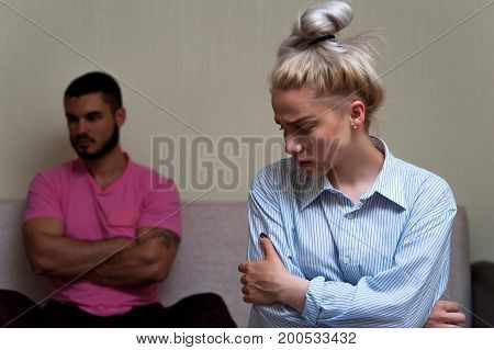 Sad young woman sitting and looking away while man sitting separately on sofa. Young couple angry at each other. Focus on female
