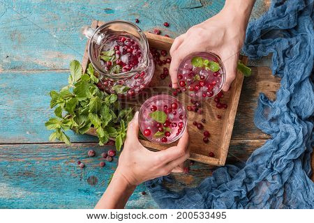 Cranberry beverage with mint, ice and berries in a box over vintage wooden background, top view