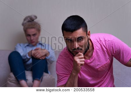 Young caucasian couple in conflict. Sad man and woman sitting separately in their living room. Focus on man