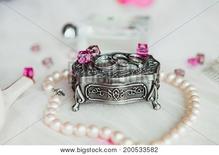 wedding ring on a cassette decrate with pink gems in white background