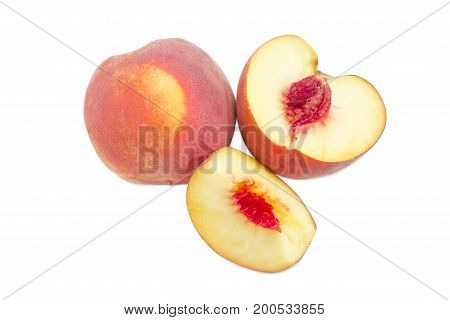 One whole and one cut into slices ripe fresh peaches on a white background