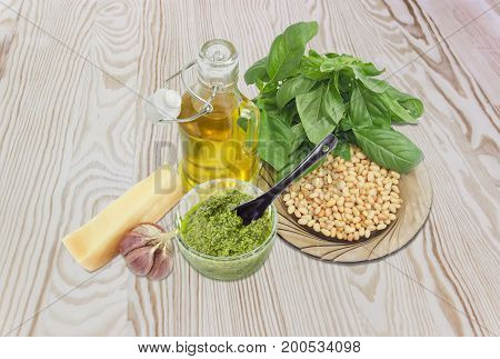 Sauce basil pesto in the small glass bowl with small black ceramic spoon on a background of ingredients for its preparation on a wooden surface
