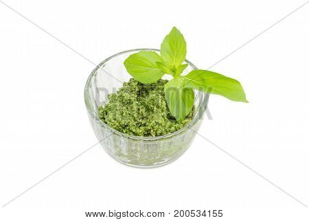 Sauce pesto in the small glass bowl decorated with green basil twig on a white background
