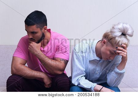 Unhappy young man and woman sitting back to back after quarrel at home. Couple having relations problems.