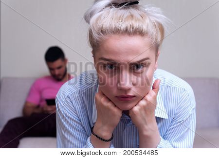 Depressed young woman sitting separately and looking at the camera while man using mobile phone. Relations problems.