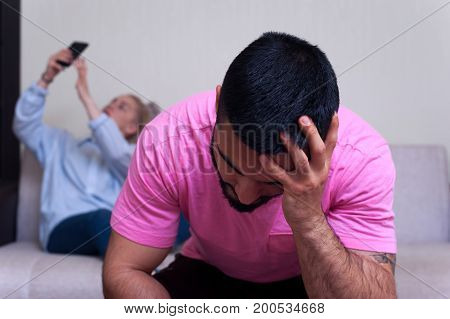 Unhappy man sitting separately in the foreground while his girlfriend using her smartphone. Young couple having relations problems.