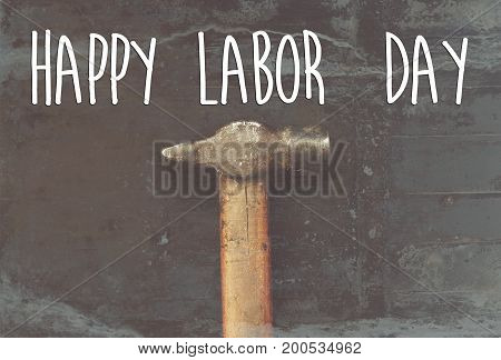 Happy Labor Day Text Sign. Hammer, Working Tool On Black Background Top View. Instrument For Hand Wo