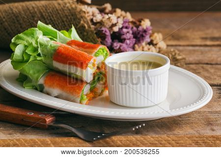 Fresh spring rolls with fresh vegetable and crab stick served with spicy salad cream dipping sauce. Rolls salad or fresh spring roll on white plate healthy delicious food for appetizer or meal. Fresh spring rolls with fusion food style.