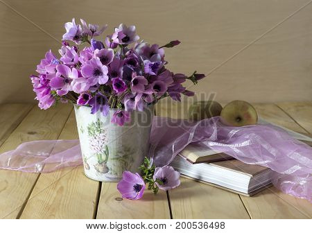 Still life with wild anemones, book and apple on a wooden table close-up