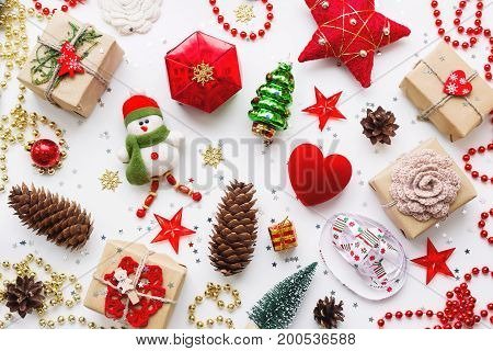 Christmas background with decorations. New Year symbol - decorative fir tree. Gifts in craft paper pine cones red hearts and confetti. Flay lay top view.