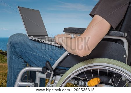 Handicapped disabled man on wheelchair is working with laptop outside.