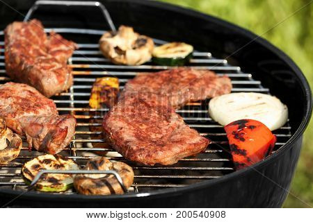 Tasty beefsteaks and vegetables cooking on barbecue grill outdoors, close up