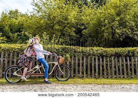Young couple riding a bike tandem in the park. Against the background of the fence from the tree.
