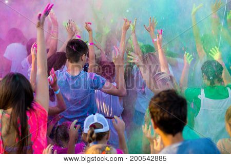 Color holi festival. Holi celebration. Clouds of colorful paint in the air. A crowd of people with their hands up
