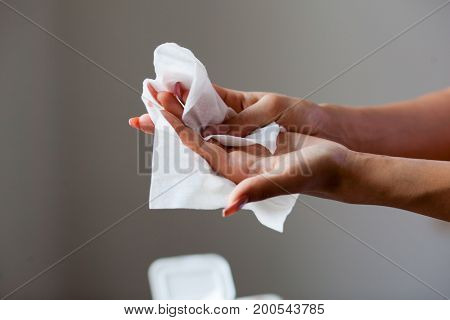 Young woman cleaning fingers and hands with wet wipes