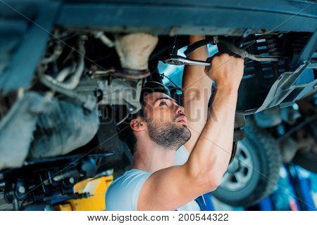 Automechanic Working On Car