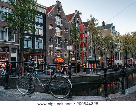 Amsterdam Netherlands - May 25 2016: Outside view of Red Light District with bridge bicycle and canal