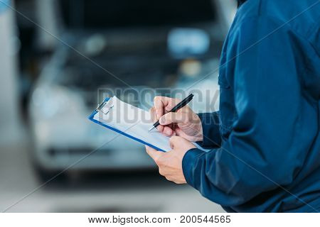 Cropped shot of a automechanic wearing overalls writing on a clipboard.