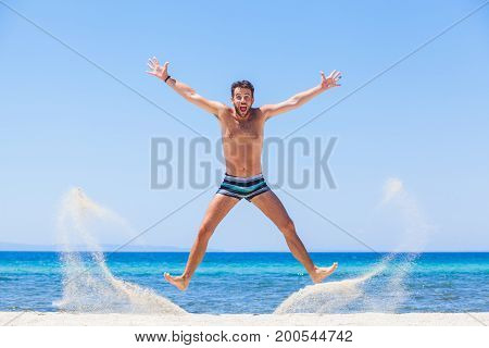 Happy young man jumping at the beach
