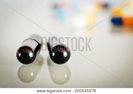 Two black isolated medical capsule lies on the white mirror surface, in front of the multicolored capsules. Closeup