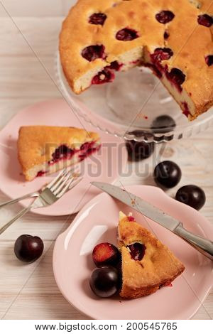 Homemade plum cake on a glass stand and pink plates. Selective focus.