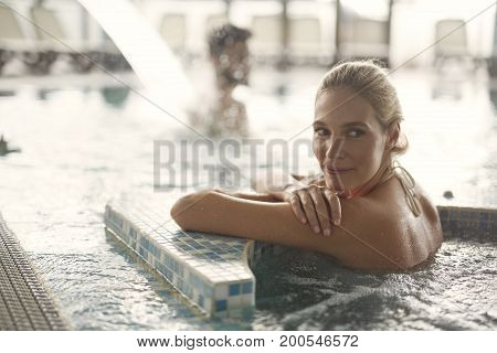 Portrait of beautiful blonde woman relaxing in jacuzzi
