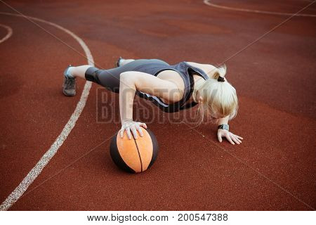 Strong Woman Doing Seated Medicine Ball Push-ups.