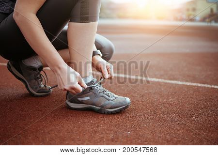 Female Runner Tying Shoe Lace In A Stadium Area.