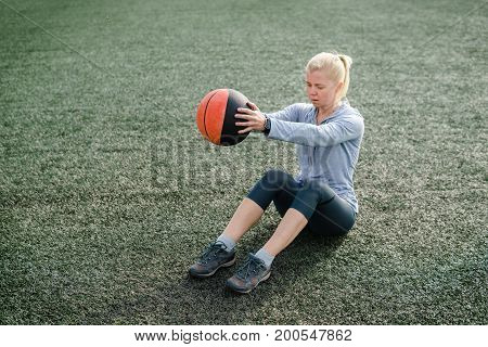 Strong Woman Doing Seated Medicine Ball Twist
