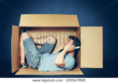 Introvert concept. The man sitting inside the box with headphones