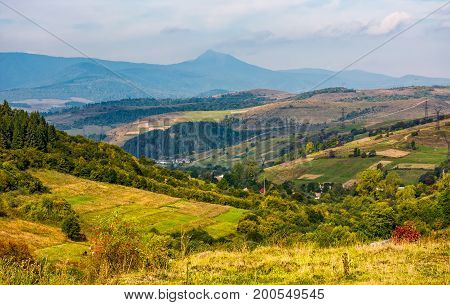 gorgeous countryside with village in valley. spectacular early autumn scenery at the foot of a mountain ridge with high peak