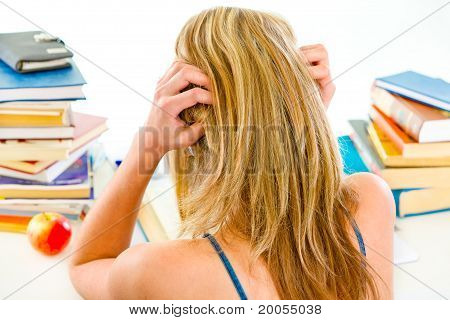 Girl sitting at table with piles of books and holding hands near head