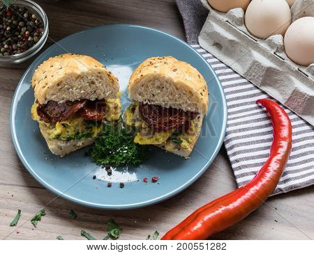 Delicious sandwich with eggs, bacon and dried tomatoes on a blue plate