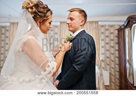 Attractive Bride Pinning Buttonhole Flower To The Groom's Jacket On A Wedding Day.