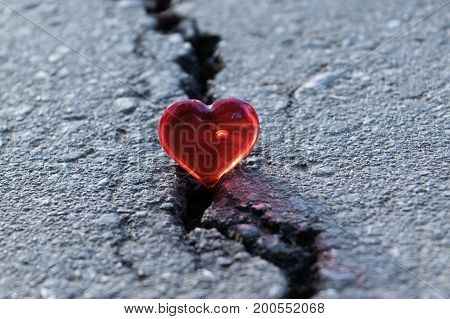 Crack on the pavement. The crack lies heart of glass. The symbol of the rupture of relations. A split or crack in love.